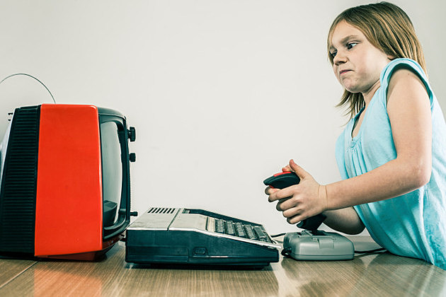 Little girl playing vintage video games with difficulty